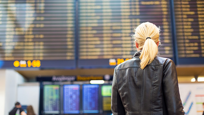 Woman at an airport looking up at the flight timetable.